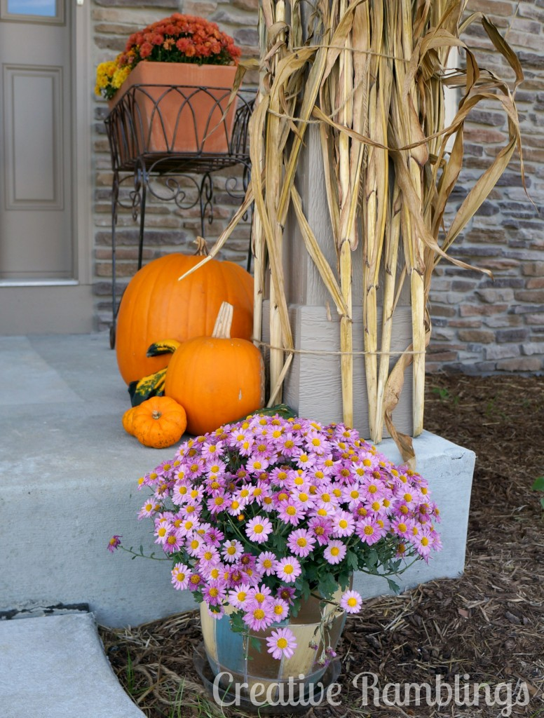 fall front porch with corn stalks pumpkins and mums