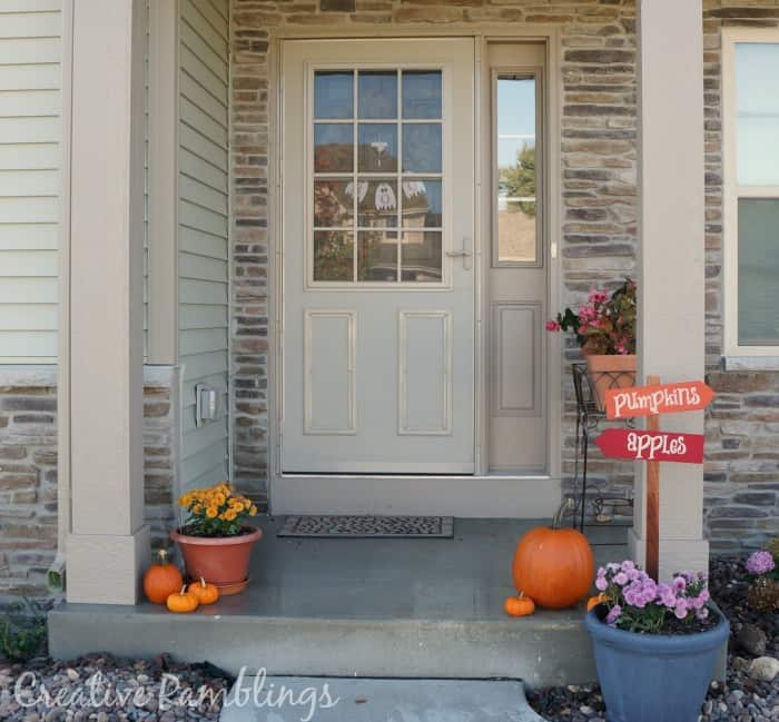 simple fall front porch with pumpkin and apple sign
