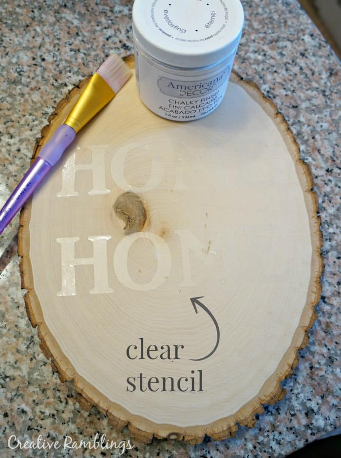 Clear con-tact paper stencil on wood slice
