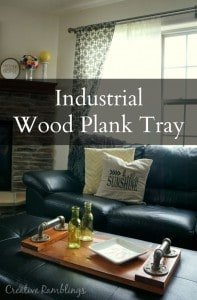 Industrial wood plank tray made with weathered wood and pipe handles.