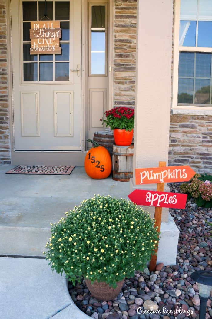 Decorate your porch with mums and pumpkins and a few rustic barrels.