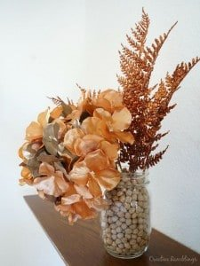 Mason jar filled with beans and metallic floral stems, perfect for fall.