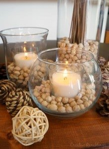 Create a warm and neutral fall centerpiece with natural textures and candles.