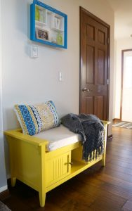 A cozy colorful foyer with a bright yellow bench.