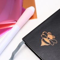 foil quill pen and bee on notebook